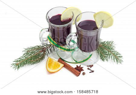 Mulled wine in two glass mug with slice of lemon mulling spices for cooking mulled wine and two fir branches on a light background