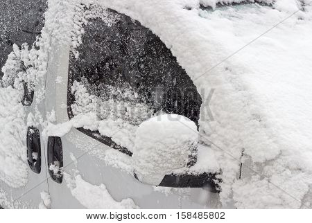 Fragment of the white car with side doors windshield and wing mirror covered with wet snow during heavy snowfall