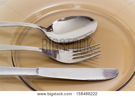 Eating utensils consisting of spoon fork and knife made from stainless steel on a dark glass dish closeup