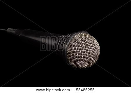 Dynamic microphone in black plastic housing with windscreen in wire mesh on a dark background