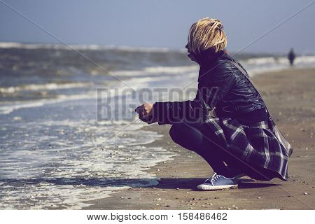 Young Caucasian blonde woman with black leather jacket and skirt crouched on sand in front of the ocean