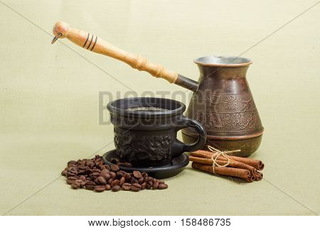 Old copper coffee pot pile of roasted coffee beans coffee in black ceramic cup with saucer and several cinnamon sticks on a hessian