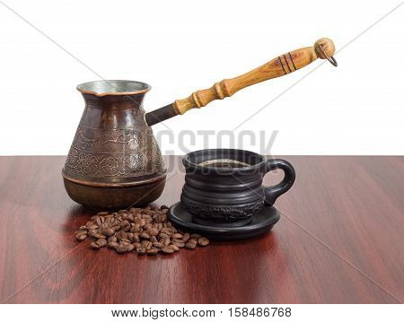 Old copper coffee pot black ceramic cup with coffee and pile of roasted coffee beans on a red wooden table on a light background