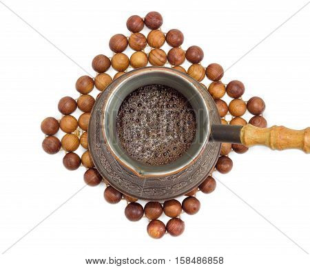Top view of freshly brewed black Turkish coffee in a old copper coffee pot on a trivet made of balls of juniper wood on a light background
