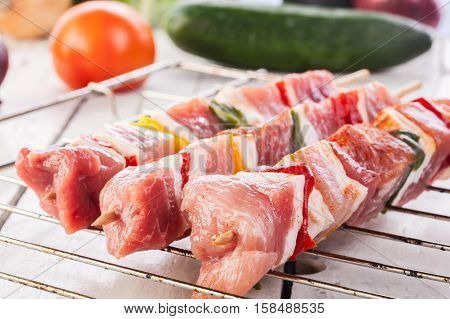 Raw shashlik and vegetables on a grill