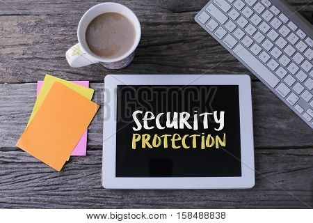 Tablet pc with security protection and a cup of coffee on wooden background