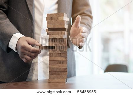 Planning risk and strategy in business businessman gambling placing wooden block on a tower with vintage tone and Risk management and insurance concept leadership has solution for problem.
