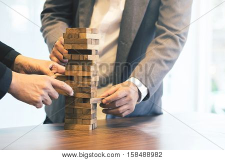 Close up of hands helping build a building of wooden pieces. Businesspeople planning a new business strategy. Business team generate new ideas with wooden bricks. Business risk concept vintage tone.