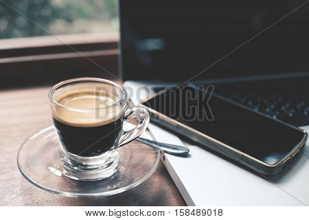 Cup of hot espresso coffee on wood table espresso brew from arabica coffee with laptop and smartphone close up shot office table with coffee morning ready for drink in the morning coffee time.
