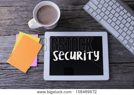 Tablet pc with security and a cup of coffee on wooden background