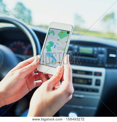 Female Driver Hands Holding A Phone With Navigator On A Screen