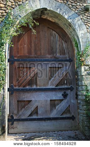 Old medieval closed castle door with stone archway and iron detail