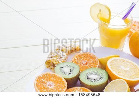 The concept of healthy breakfast orange juice fruit and cereal bars clouse up on wooden table with copy space. Good morning still life. Wonderful breakfast energy boost for the day.