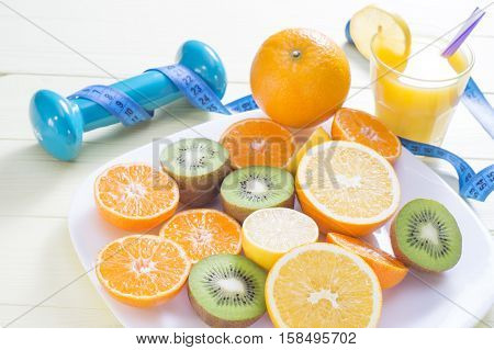 The concept of healthy lifestyle. Orange juice fruits. cereal bars dumbbell and measuring tape on yellow wooden table. Cereals and fruits - diet and breakfast