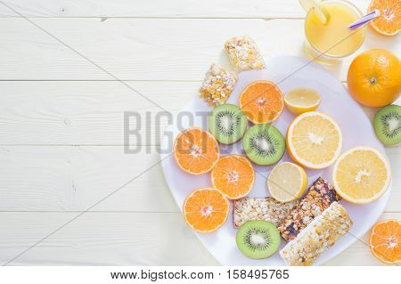The concept of healthy breakfast orange juice fruit and cereal bars flat lay on wooden table with copy space. Good morning still life. Wonderful breakfast energy boost for the day.