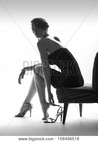 Beautiful sitting woman with high heel shoes, white background