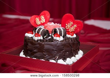 Black forest cake whole pastry decorated with whipped cream, red cherry, double happiness, and shuang xi love heart