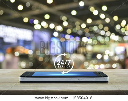 24 hours service icon on modern smart phone screen on wooden table over blur light and shadow of shopping mall Full time service concept