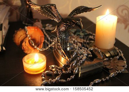 beautiful big silver color metal eagle with wide open wings stay between two burn candles decoration on holiday