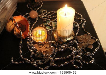 decoration for holiday night two bright burn candles, silver chaplet, flowers, crystals, shells