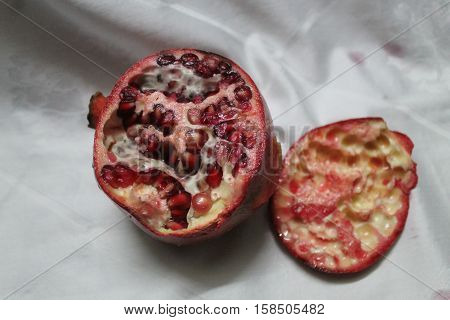 big juicy ripe dark red color pomegranate with crystals full of sweet liquid grains inside prepare for meal