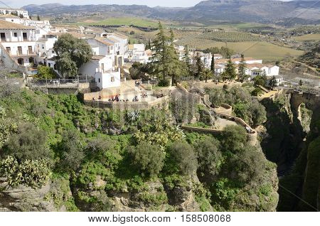 RONDA, SPAIN - MARCH 1, 2014: People walking by the path next to the gorge in Ronda Andalusia Spain