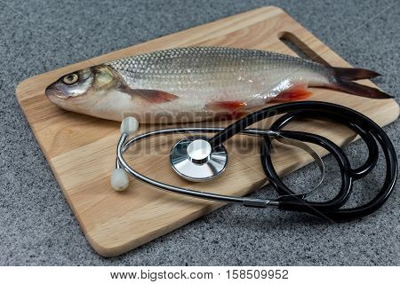 Raw fish not cooked. Fish on a cutting Board lying next to a stethoscope. The doctors recommend. Symbolizes allergic to fish or artificiality of food or the risk of infection when consuming fish. The need for medical care.