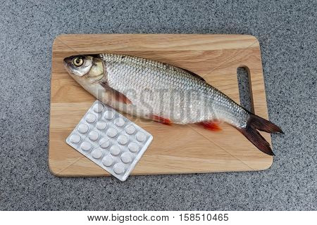 Raw fish not cooked. Fish on a cutting Board lay next to the pills. Symbolizes allergic to fish or the contamination of food unnatural food. Or the risk of infection when consuming fish.