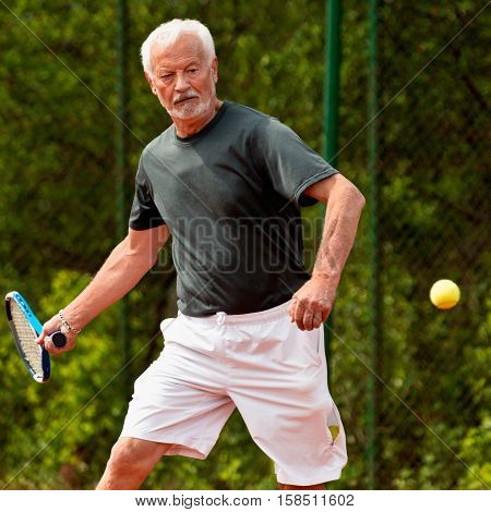 Senior tennis player playing tennis, toned image, outdoors