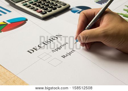 Businessman hold pen for approve and reject decision with calculator and finacial graph support