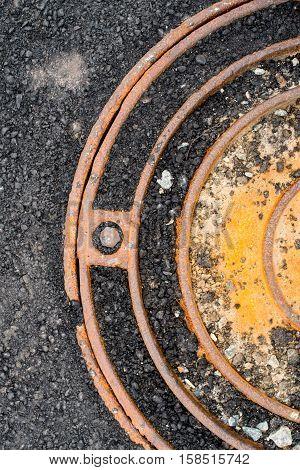 Rusty metal manhole cover in black asphalt surface