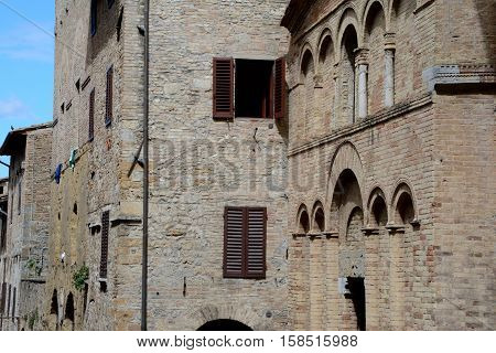 San Gimignano Italy - September 6 2016: Buildings in San Gimignano city in Tuscany Italy. Unidentified people visible.