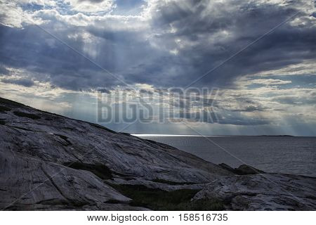 The sun's rays make their way through the clouds over the sea and the rock, after the storm