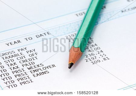 Pencil on the statement of payroll details. Financial accounting concept.