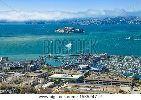 Aerial view of Alcatraz Island, Hyde Street Pier in Fisherman's Wharf and Maritime National Historical Park, from top of Coit Tower on sunny day. San Francisco, California, Unites States.