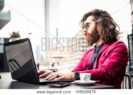 Young hipster man working at pc laptop in a cafè outdoors