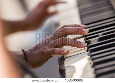 closeup on woman hands playing the piano expertly