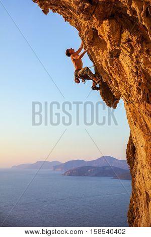 Rock climber on overhanging cliff. Kalymnos Island, Greece.