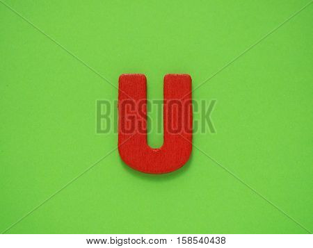 Capital letter U. Red letter U from wood on green background. Alphabet vowel.
