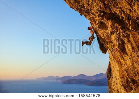 Rock climber jumping on handholds while climbing overhanging cliff