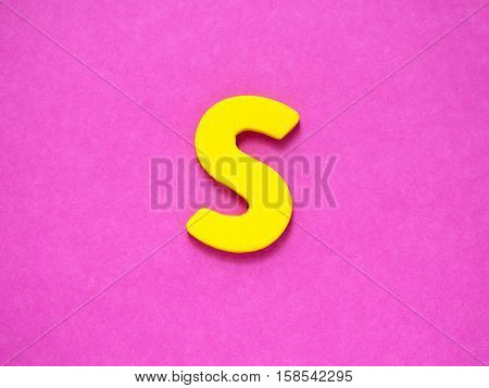 Capital letter S. Yellow letter S from wood on purple background.