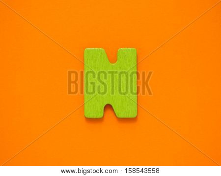 Capital letter N. Green letter N from wood on orange background.