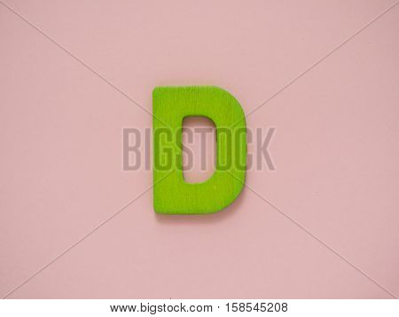 Capital letter D. Green letter D from wood on pink background.