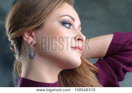 profile portrait of beautiful woman wearing ethnic silver earrings