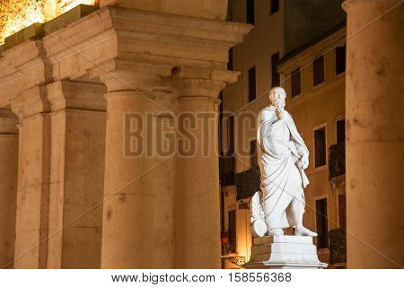 Night view of the statue of the famous Renaissance architect Palladio seen through some columns of the Palladian basilica Vicenza