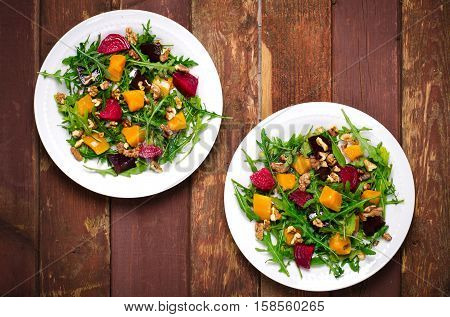 Fall salad with greens, arugula, walnuts, beetroot and roasted squash, pumpkin on wooden background, rustic style