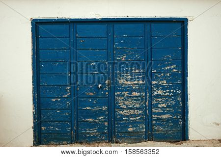 Blue wooden door worn by the passage of time