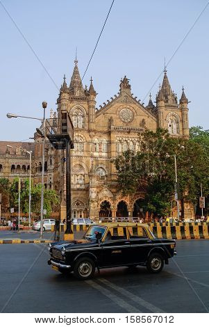Mumbai, India - January 1, 2012: Famous Mumbai yellow-black taxi car and at background Chhatrapati Shivaji Terminus (CST) is a UNESCO World Heritage Site and an historic railway station in Mumbai