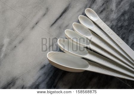 Set of white plastic measuring spoons in a fan shape showing imperial and metric measurements isolated on marble background