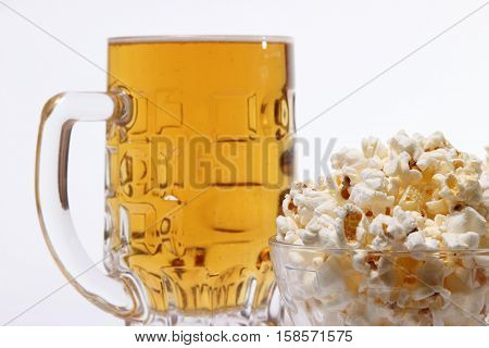 pint of cold light beer and salty popcorn on a white background